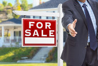 Male Agent Reaching for Hand Shake in Front of For Sale Sign and House