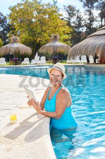 Senior Frau im Pool mit Tablet Computer