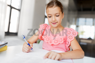 student girl with book writing to notebook at home