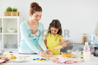 happy mother and daughter making cookies at home