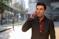 Young handsome Hispanic businessman thinking while talking on the phone outdoors