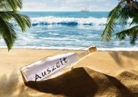 Flaschenpost mit der Nachricht Auszeit am Strand