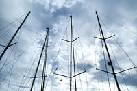 Ship masts over blue cloudy sky background