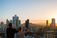 couple looking above city skyline with sunset sky from skyscraper
