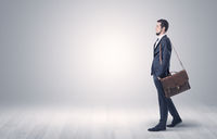 Businessman walking in front of an empty wall