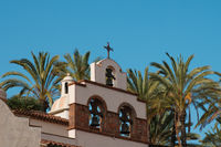 cross on church / monastery bell tower with palm tree and blue sky background -