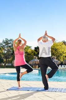 Senioren am Hotel Pool machen Yoga Übung