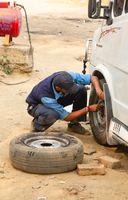 A man fixes a wheel at the car
