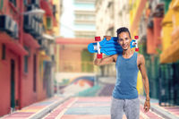 Lifestyle concept portrait of young handsome man holding skateboard standing on city street