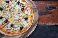 Top view of fresh tasty pizza with mushrooms, olives, paprika and mozzarella cheese on rustic wooden table