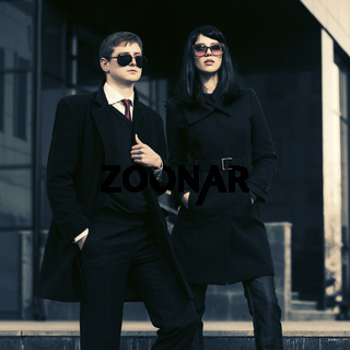 Young fashion business couple against office building
