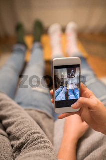 close up of couple taking foot photo by smartphone
