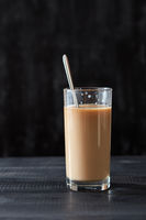 Delicious coffee with milk in a glass with a spoon on a black wooden table with copy space