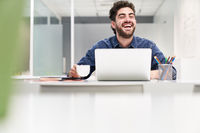 Lachender Student oder Entrepreneur am Laptop