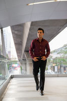 Handsome Hispanic businessman walking and thinking on the footbridge
