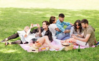 friends with smartphones on picnic at summer park