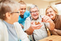 Gruppe Senioren spielt mit einem Holzpuzzle