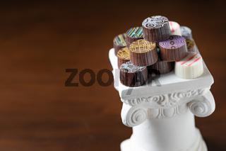 Stack of Fine Artisan Chocolates Stacked On White Pillar Column