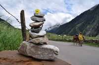 LADAKH, JAMMU AND KASHMIR, INDIA, July 2018, Local man pass by stone pyramid made with loose stones for good fortune.