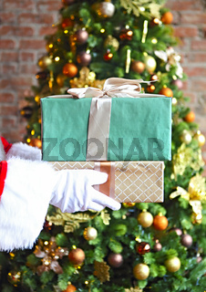 Santa Claus secretly putting gift boxes by the Christmas tree