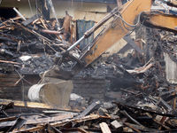 Hydraulic crusher excavator machinery working on a demolition site clearing burned debris with dust and smoke