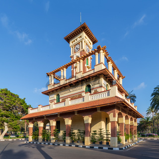 Clock tower in Montaza public park with decorated stone wall, green wooden window shutters, and red tile canopies, Alexandria, Egypt