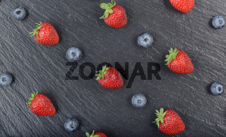 Flat lay view at ripe bilberry and strawberries on slate stone tray closeup