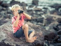 Little boy looking far away with binoculars