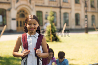 Beautiful little schoolgirl standing with rucksak