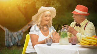 The Old Couple Is Sitting At The Table in The Beautiful Garden And Talking.
