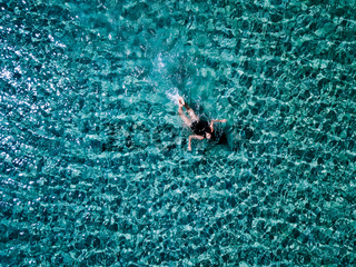 Young girl in a black swimsuit swims in the sea.