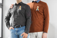 close up of couple with gay pride rainbow ribbons