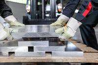 Workers taking aluminium billet