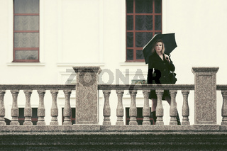 Young fashion woman in black coat with umbrella walking in city street