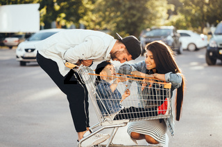 Young parents put their son in a cart and have fun in the parking.