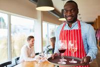 Kellner serviert Gläser mit Wein auf einem Tablett