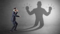 Businessman fighting with his unarmed shadow