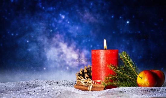 Kerze mit Weihnachtsdekoration vor Sternenhimmel