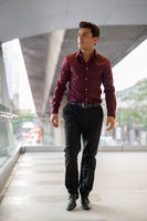 Young handsome Hispanic businessman thinking and walking on the footbridge
