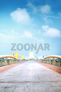 Abstract photo of empty road over bridge with cityline on the background