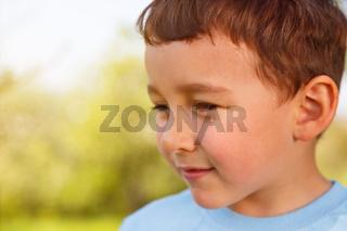 Kind kleiner Junge Textfreiraum Copyspace schaut zur Seite Portrait Gesicht draußen