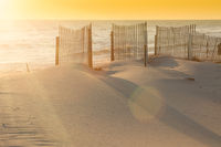 Beautiful Sunset Over the Ocean with Sand Fencing