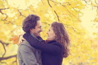 Smiling couple hug in autumn forest