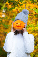 Teenage girl holding halloween pumpkin