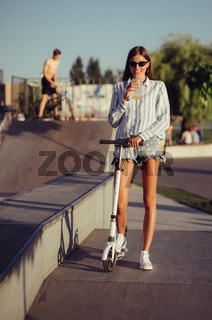 Beautiful girl with scooter posing on camera.