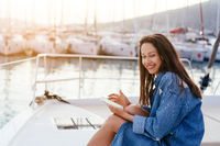 Young beautiful girl is sitting on the deck of a yacht with a smartphone