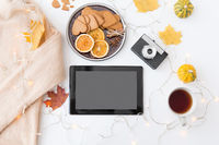 tablet computer, camera, autumn leaves and garland