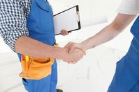Two construction workers shaking hands