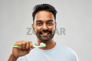indian man with toothbrush over grey background