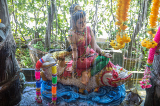 Phra Mae Thorani, goddess from Buddhist mythology, behind water of fountain.